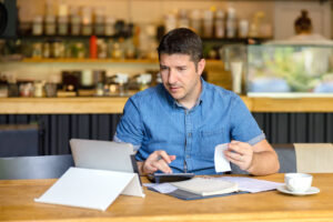 Small business owner calculating finance bills of new business start up