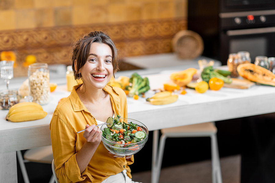 Young and cheerful woman eating vegetable salad.