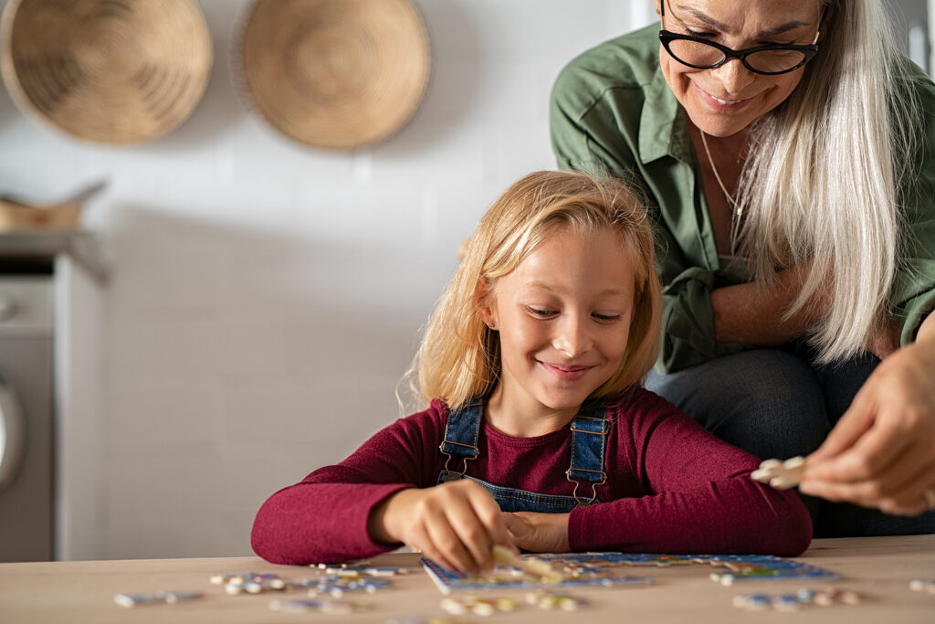 Grandmother and granddaughter doing puzzle together at home