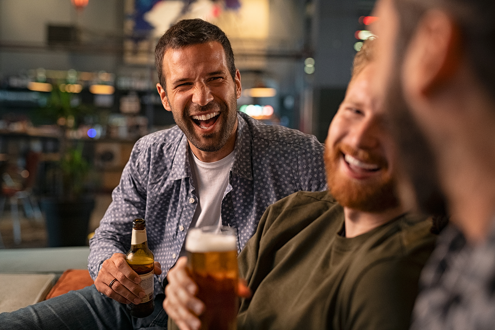 Happy young men drinking beer while having fun in a pub