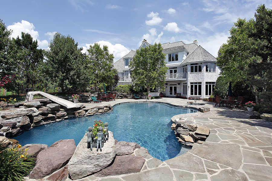 Rear view of luxury home with swimming pool