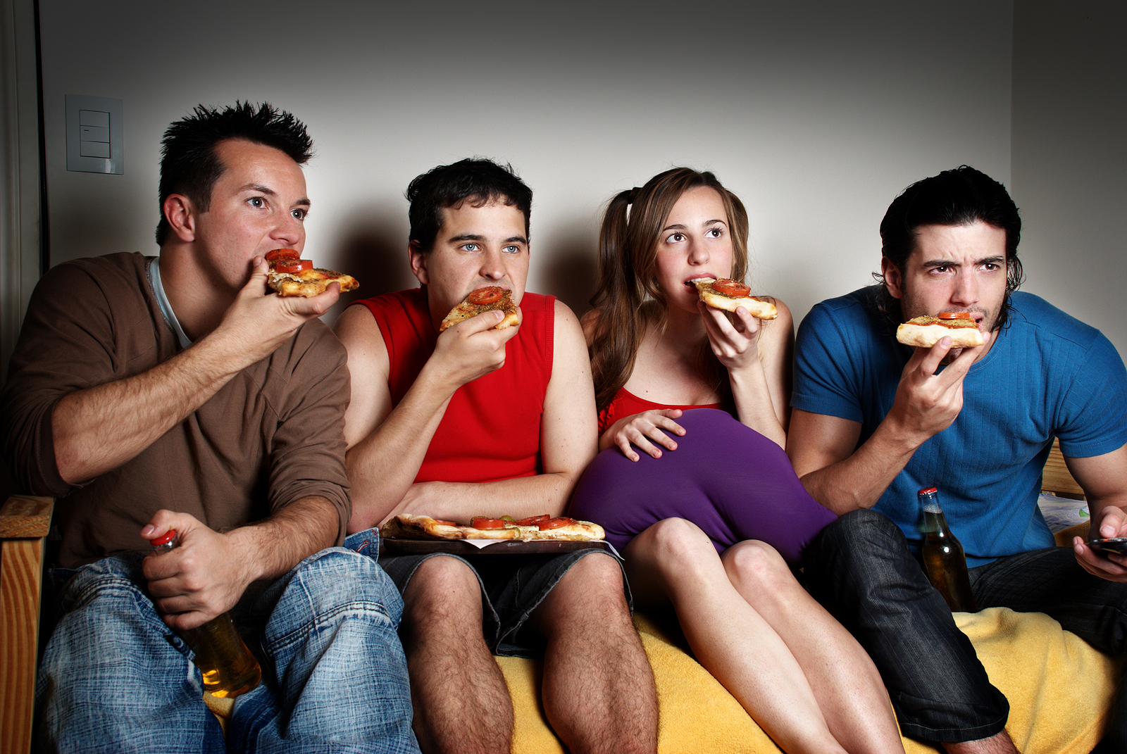 Four concentrated fans with a pizza in hands, watching TV