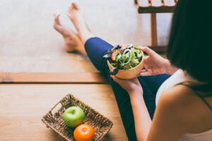Woman holding and eating healthy salad for breakfast.