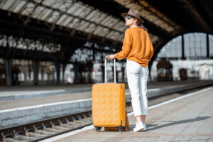 Young female traveler standing with a suitcase at a train station alone.