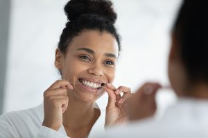 Beautiful smiling african woman holding dental floss cleaning teeth
