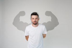 Shade of muscular powerful and strong silhouette with big arms behind a man. Concept of Inner Strength