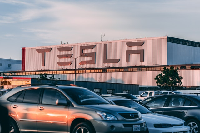 A group of Tesla cars out the front of the sign created by Elon Musk.