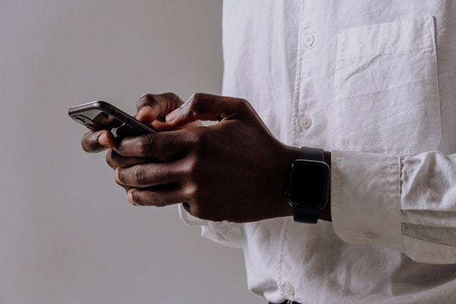 A man holding a smartphone using some of the apps he has downloaded.