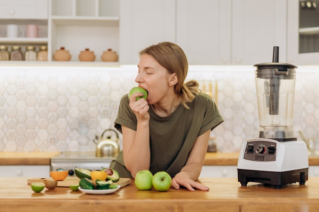 A woman with vegan fruit, vegetables and a blender leaning against the counter eating an apple.