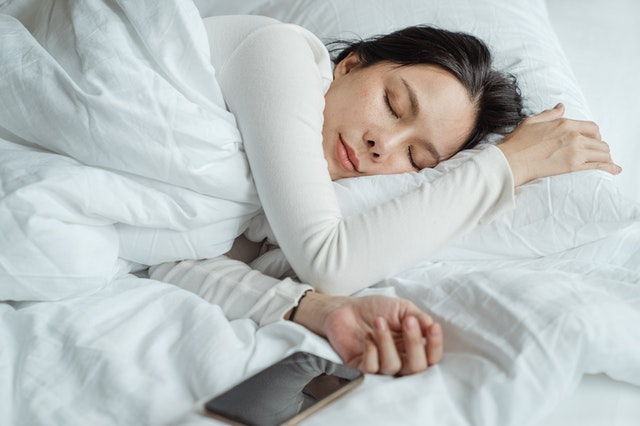 A woman asleep in bed with her smartphone next to her ready for her alarm app to go off.