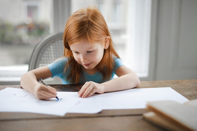 A young girl sitting at a desk writing down her work from her online tutor on a piece of paper