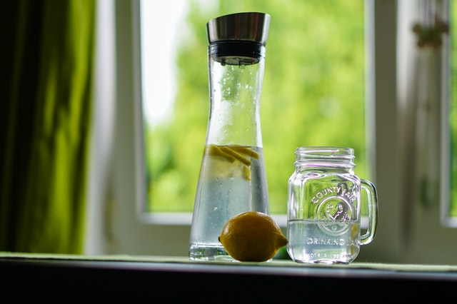 A glass and a jug of detox water on a table with a lemon next to them.