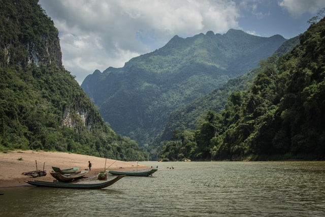 Scenery of Laos mountains and a lake with boats. Laos can be visited on a budget.