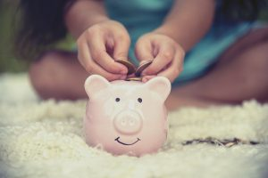 Adorable kid saving coins in piggy bank.