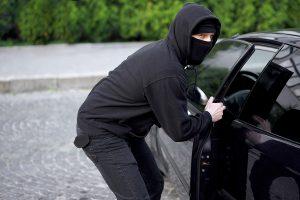A man in hoodie hijacking a car