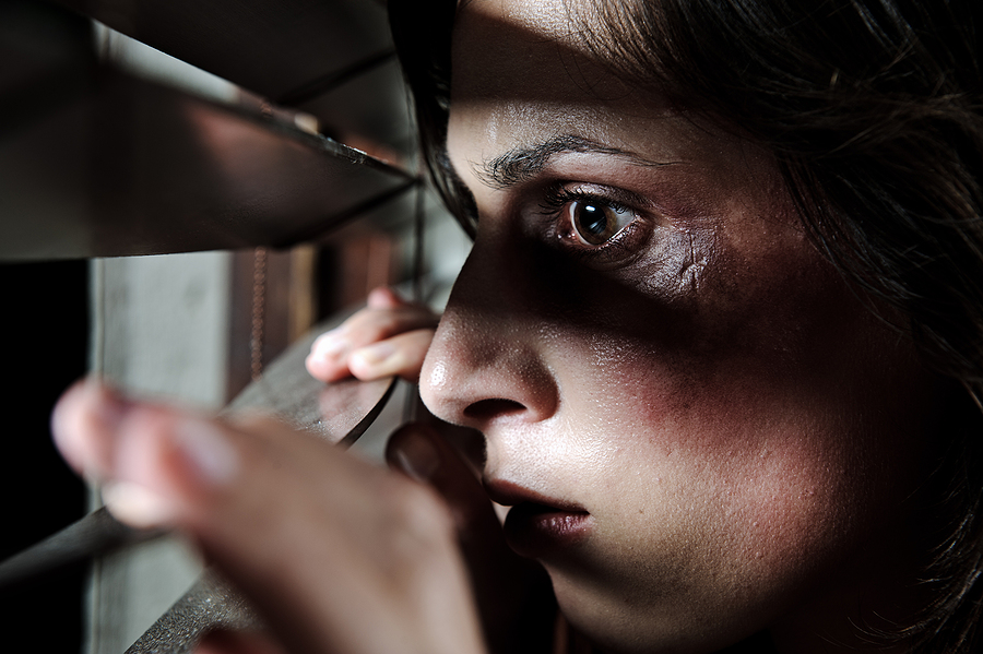 Fearful battered woman peeking through the blinds