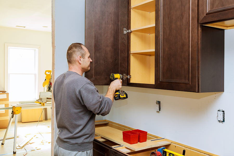 Repairman installing cabinet in the kitchen