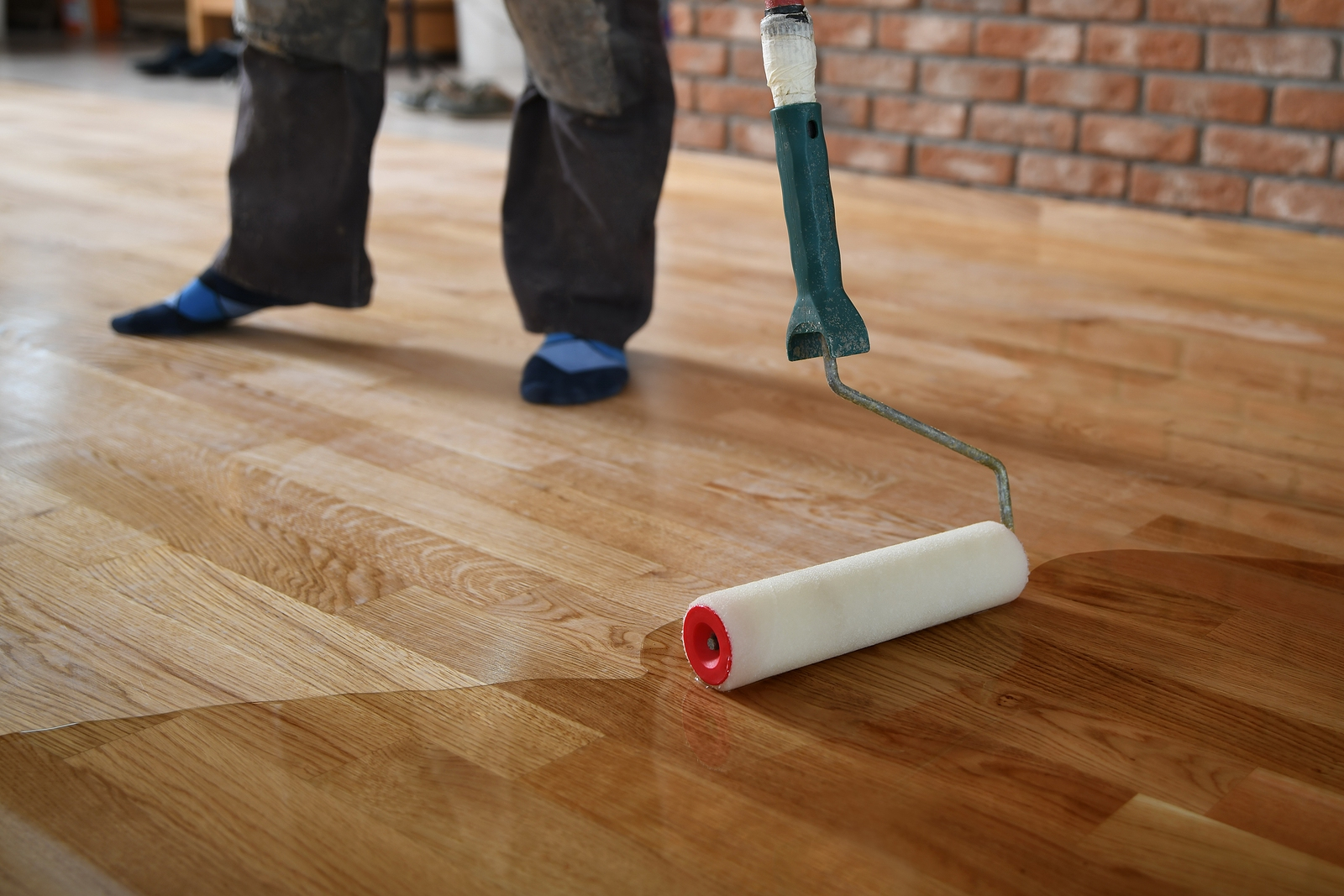 Worker lacquering wood floors