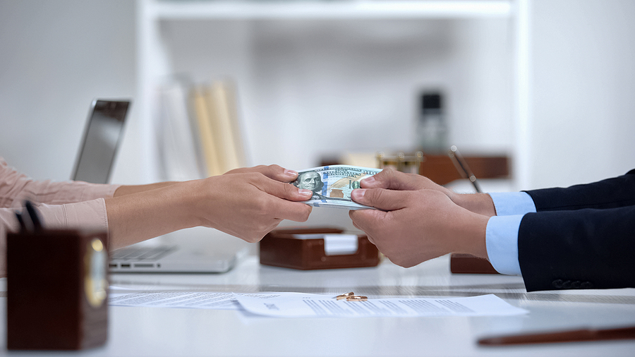Couple hands pulling money, dividing marital property during divorce