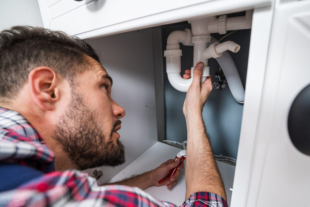 Male plumber fixing a blocked pipe
