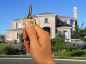 Woman holding a house key with a new home in the background