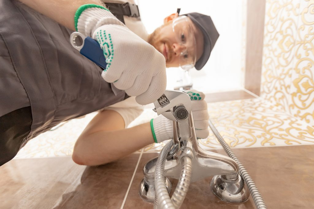 Plumber installing shower stall
