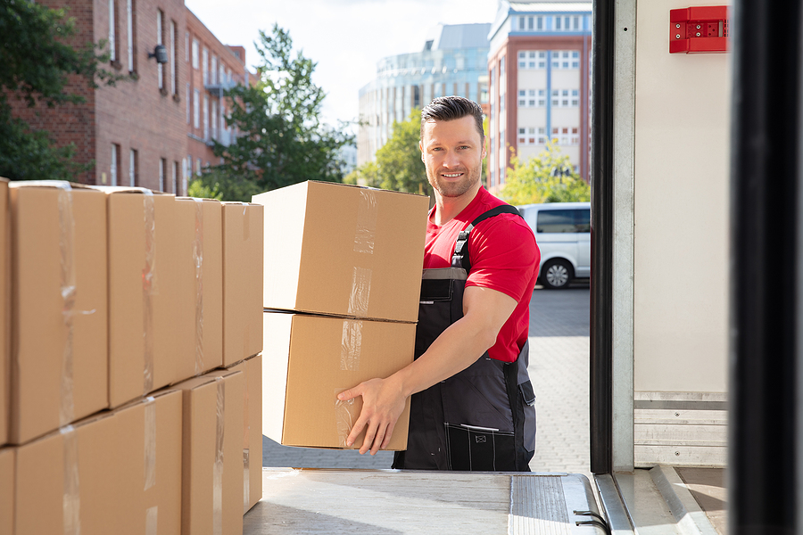 Mover in uniform carrying boxes