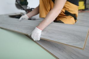 Repairman installing laminated panels flooring in a home