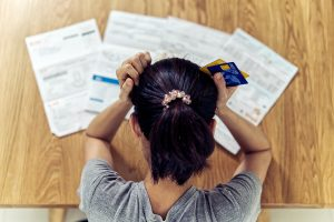Stressed woman worrying about credit card debt and all loan bills.