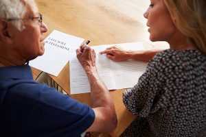 Woman helping a senior man complete his last will and testament