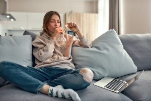 Young woman sitting on the couch and smoking using a bong