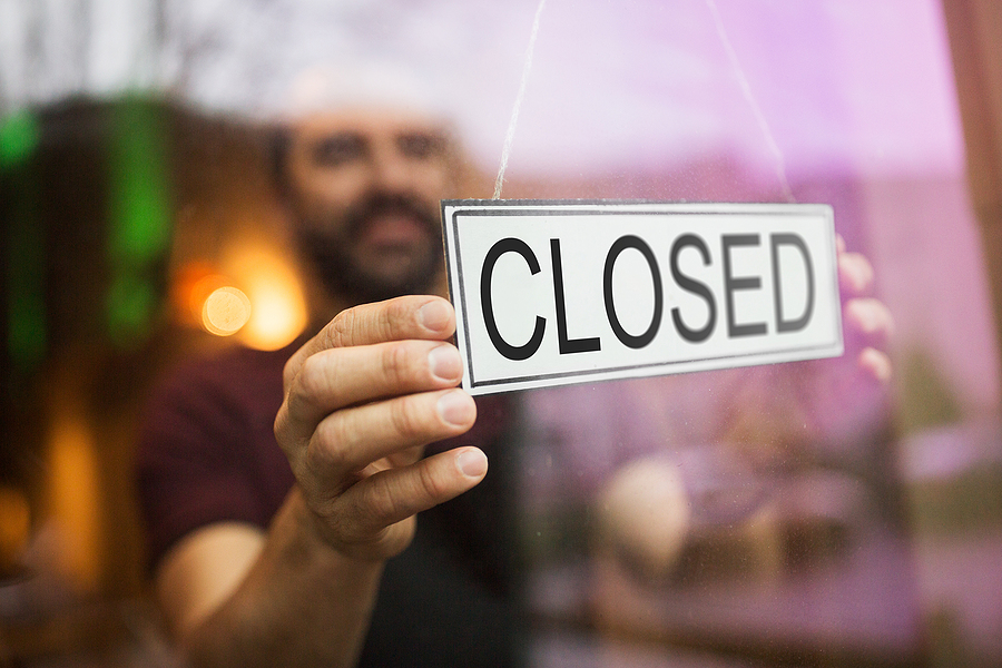 Restaurant owner owner puts closed sign at the glass door