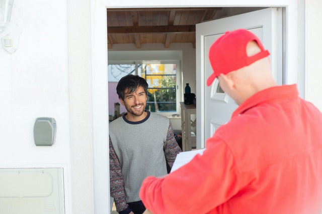 Delivery man standing with Amazon package at the door while a man opens the door and smiles.