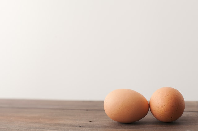 Two eggs on a wooden table. They are the best foods for weight loss.