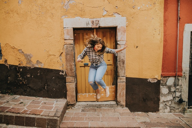 A woman in front of a door jumping in the air as she is playing a forgotten childhood game the floor is lava.