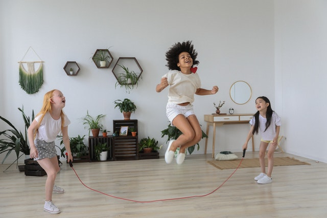 Three kids laughing as the jump playing skipping rope a forgotten childhood game.