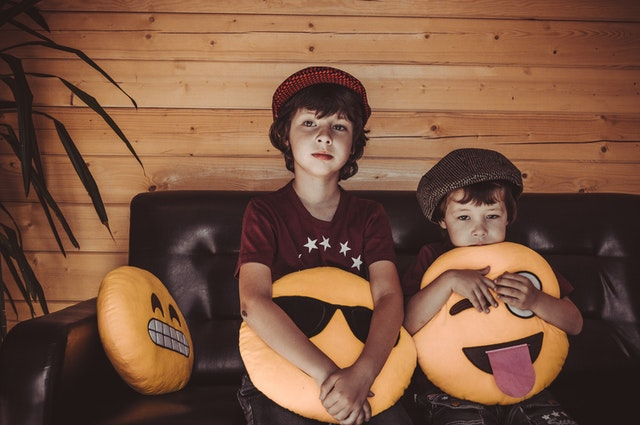 Two boys sitting on a couch holding popular emoji pillows.