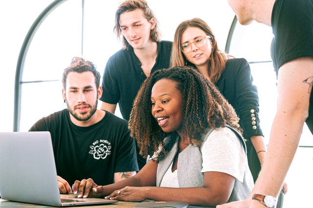 A team of young people standing around an open laptop deciding how to market and release the app they have developed.