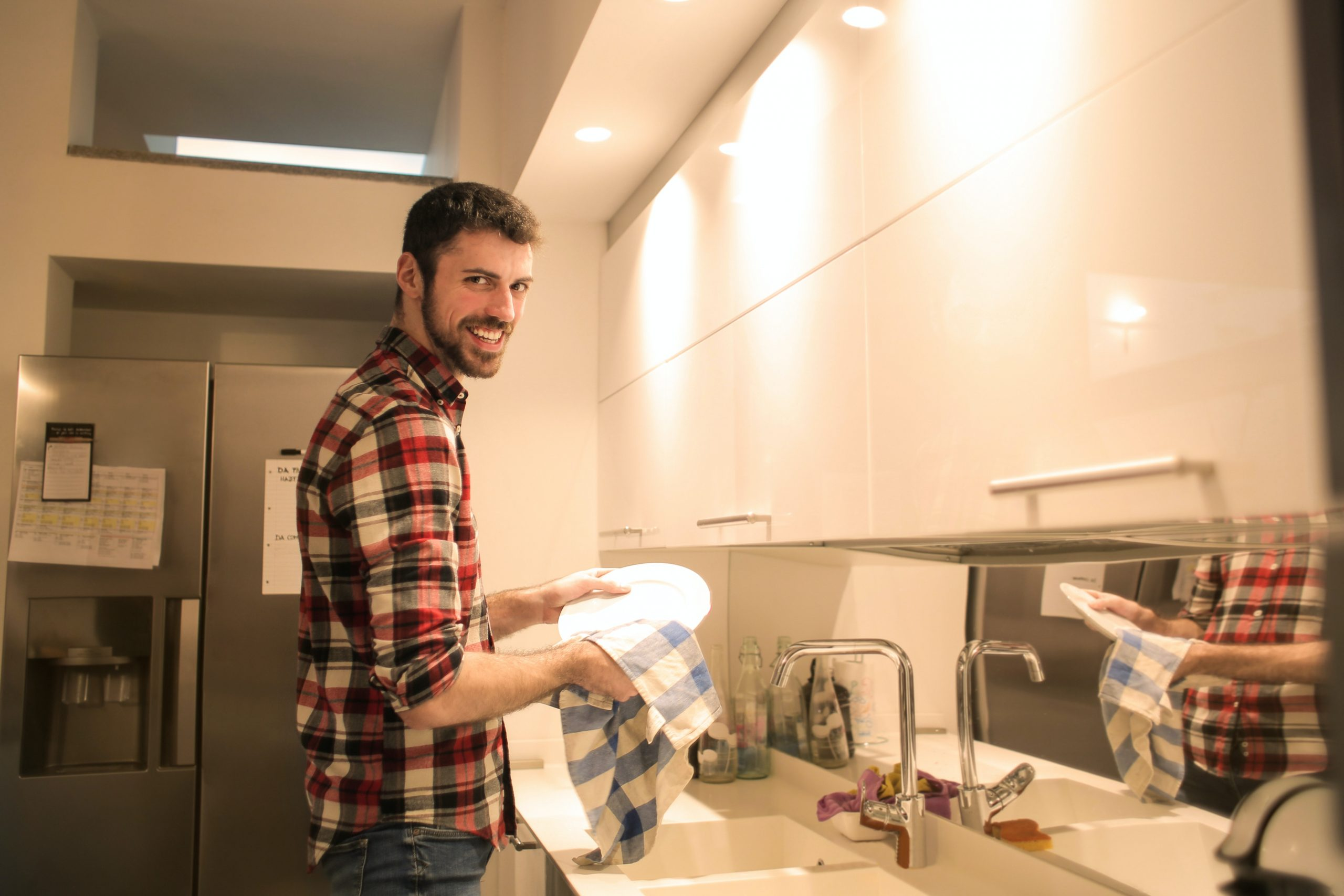 Man while cleaning a plate in the kitchen