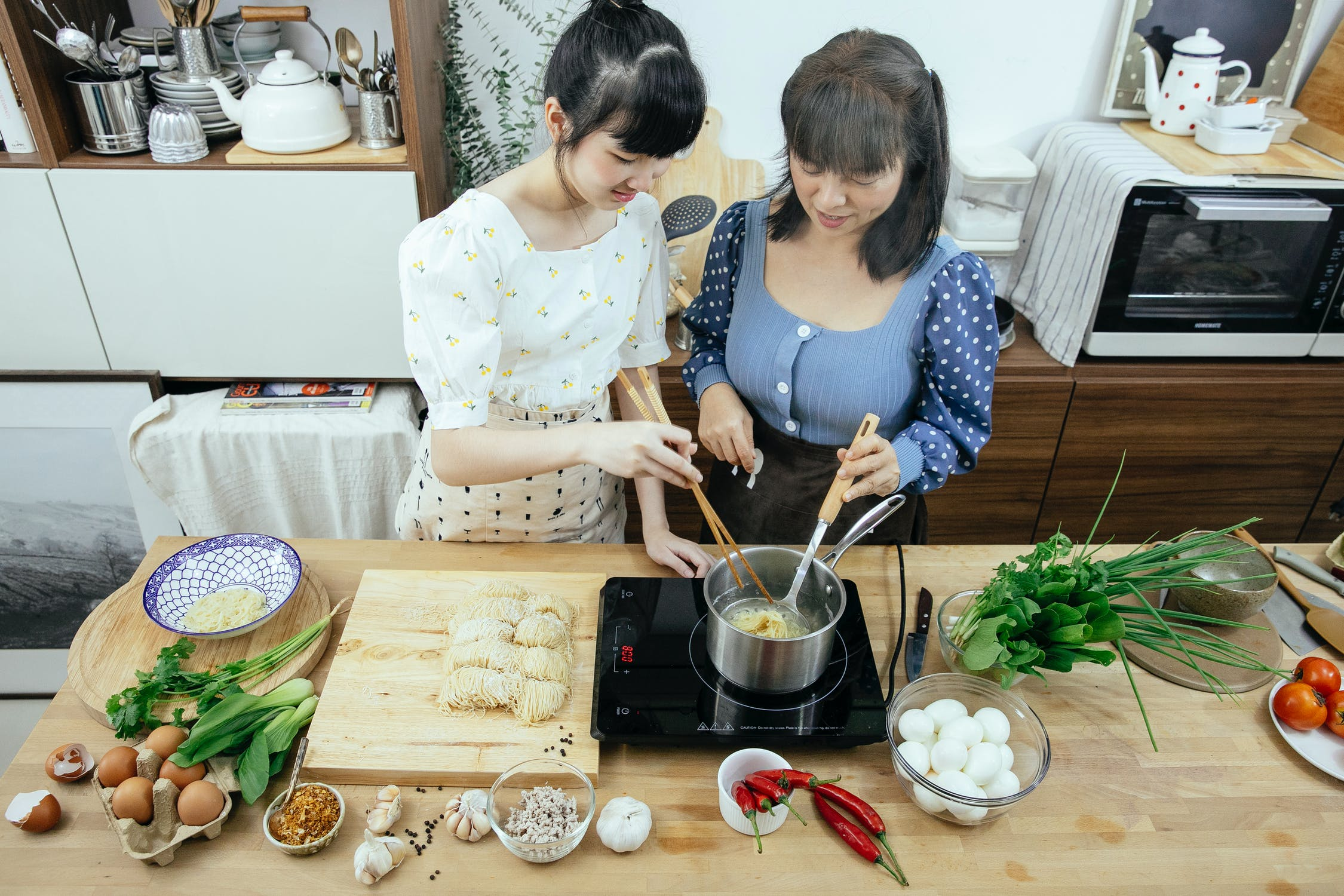 Two women improvising recipe in the kitchen
