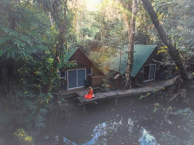 A woman visiting Guatemala on a budget sitting on a wooden deck out the front of two houses in a rainforest.