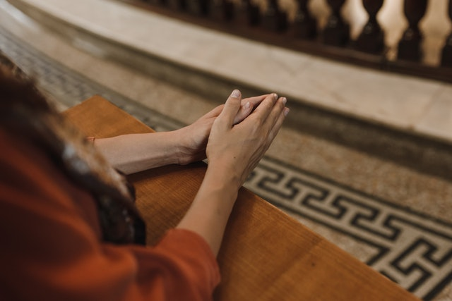Woman praying with hands together to reconnect with faith.