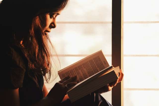 A girl reading a book as it is better than watching a movie.
