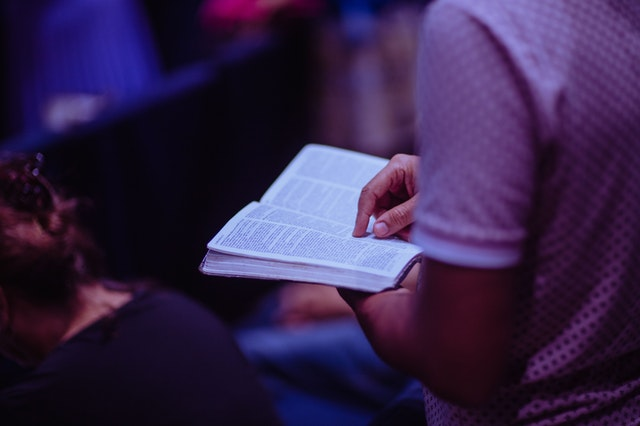 A man reading a Holy book dedicating time to practice and reconnect with his faith.