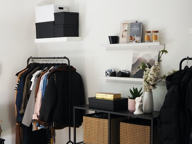 A capsule wardrobe in a bedroom next to a shelf of items. It has been created on a budget.