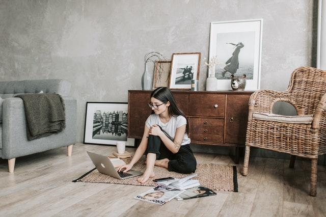 A woman sitting on the floor with her laptop and magazines around her selling her unique product on Amazon.