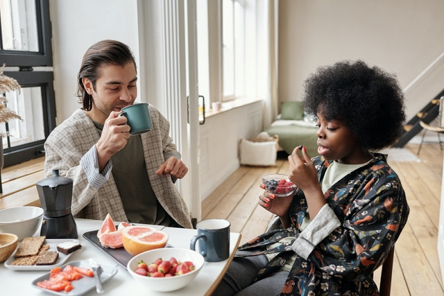 Two vegans sitting at a table with fruit and vegan food sipping coffee and eating.