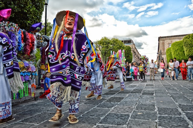 People wearing traditional Mexican dress parading on a street. Mexico can be traveled to on a budget.