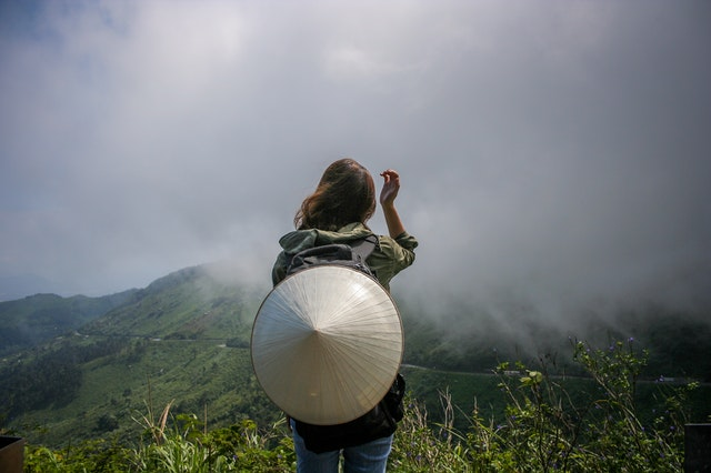 A woman with a hat on her back standing in front of mountains on her budget holiday in Vietnam.