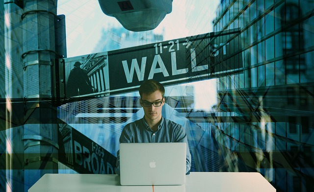 A man sitting at a laptop on Reddit with a Wall Street background behind him.